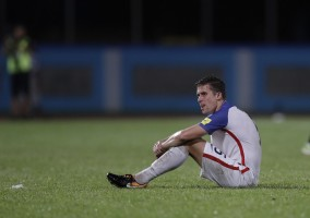 United States' Matt Besler, squats on the pitch after losing 2-1 against Trinidad and Tobago during a 2018 World Cup qualifying soccer match in Couva, Trinidad, Tuesday, Oct. 10, 2017. (AP Photo/Rebecca Blackwell)